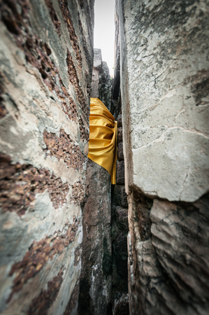 si: Closeup yellow fabric bind of stone wall, Traditional buddhism style in temple