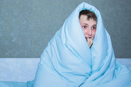 young guy sitting on a bed wrapped in a blue blanket. Stock Photo