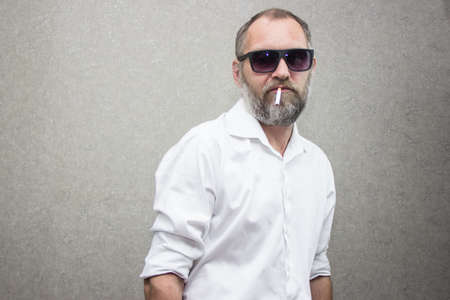 A man in a shirt with a beard in glasses smokes a cigarette 免版税图像
