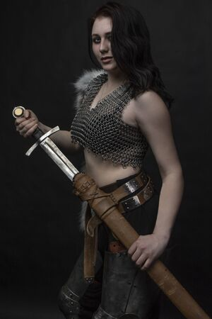 girl knight in chain mail with fur with a sword in her hands 版權商用圖片