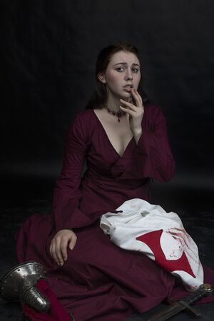 girl in a red dress cries over the things of the deceased knight