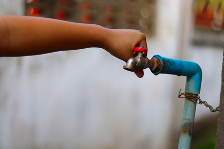 Young hands turning off an old rusty water tap for saving water - save water concept - ecological and environmental concept
