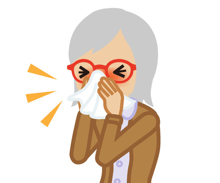 Senior woman blowing nose with a tissue
