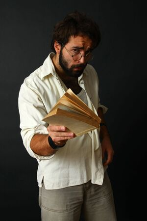 expressive man with a book on black background photo