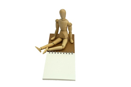 Wooden doll sitting on a notebook in white background. Stock Photo