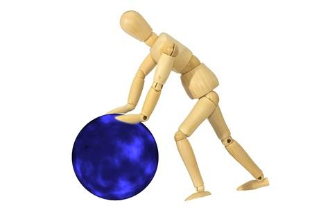 marioneta de madera: Mu�eco de madera en pie sobre un fondo azul y un carro de bolas blancas. Foto de archivo