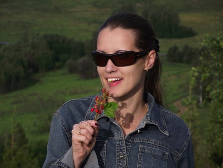 The beautiful young woman in dark glasses tries wild strawberry photo