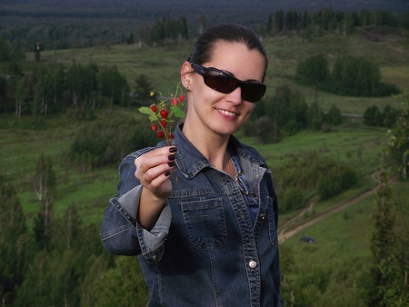 The beautiful smiling young woman holds in a hand a branch with wild strawberry berries photo