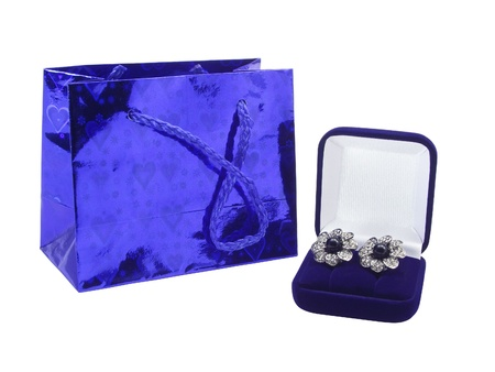 Package for gifts and an earrings in a box on a white background photo