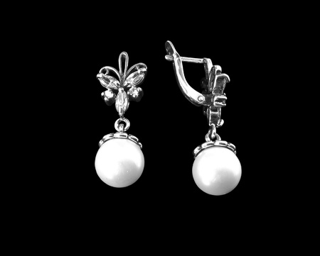 Silver earrings with pearls on a black background photo