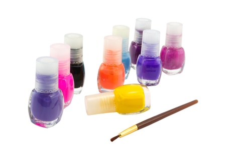 Nail polish of different colours and brush on a white background photo
