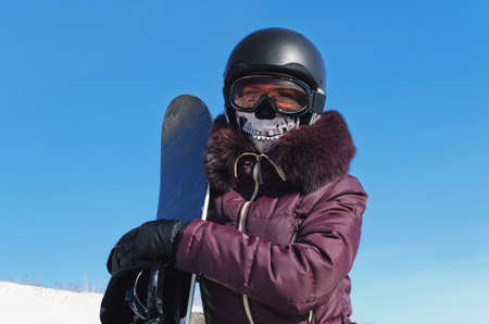 The young woman with a snowboard, in a helmet, in a ski glasses and in a ridiculous ski mask on the blue sky background photo