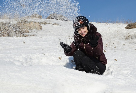 The beautiful young woman in mountain-skiing clothes has fun throwing upwards snow photo