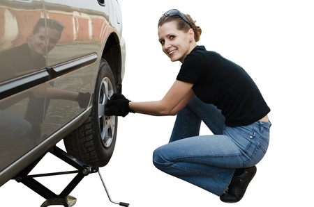 The beautiful young woman removes a wheel of the car near garage photo