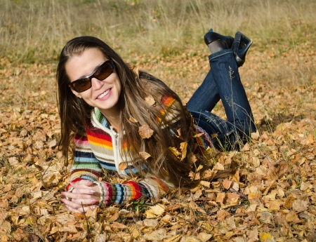 The beautiful smiling young woman in dark sun glasses lies on yellow autumn leaves  photo