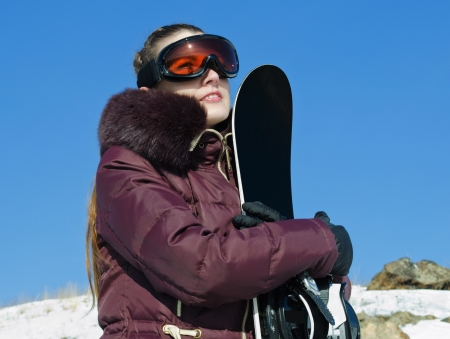 The young woman with a snowboard, in a helmet, in a ski glasses  on the blue sky background photo