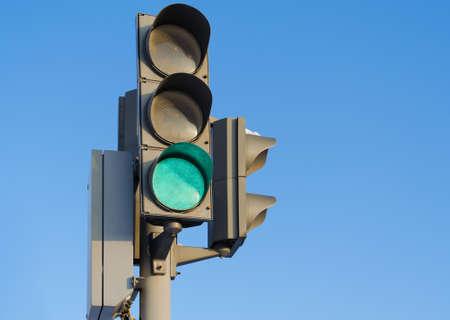 señal de transito: Semáforo contra el cielo azul con la quema de luz verde