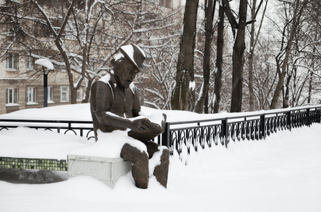 The sculpture the man reads the book in city park in the winter, under snow photo