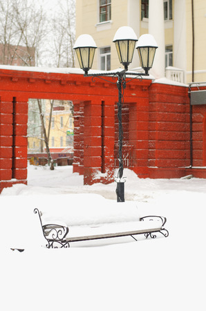 snowlandscape: Kind on snow-covered city square with a lantern and a bench