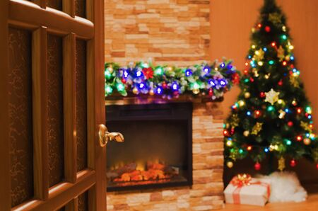 mantel: The view into the room with an electric fireplace and a Christmas tree through the open door Stock Photo