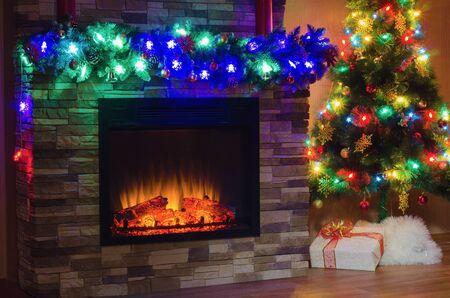 camino natale: Camino elettrico e l'albero di Natale, decorato con ghirlande con luci colorate Archivio Fotografico