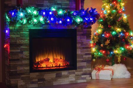 christmas fireplace: Electric fireplace and Christmas tree, decorated with garlands with colored lights