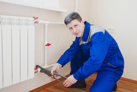 plumber: The plumber connects the radiator in the apartment. he looks at the camera