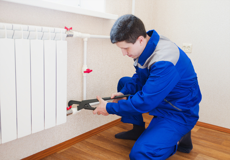 plumber: A plumber performs the installation of radiator heating in the new apartment