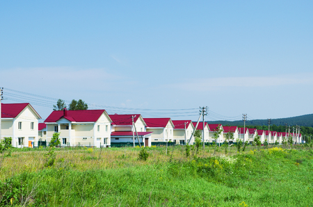 residential house: New village of similar houses, built along the road. Summer Sunny day. Russia
