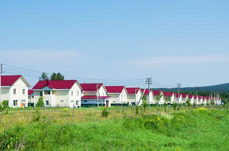 case moderne: Nuovo villaggio di case simili, costruita lungo la strada. Giornata di sole estivo. Russia Archivio Fotografico