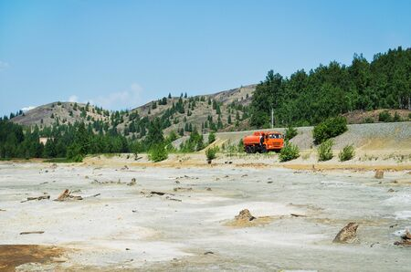 poisoned: the truck is moving over rough terrain where there is little green vegetation and the soil poisoned waste metallurgy