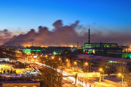 production area: Night landscape with a road in the industrial area of the city and buildings and production halls on the background. View from the top. City  Nizhny Tagil. Russia Stock Photo
