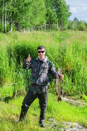 flare up: Happy Fisherman in sunglasses and high rubber boots poses for the camera with his pike, raising the thumb up