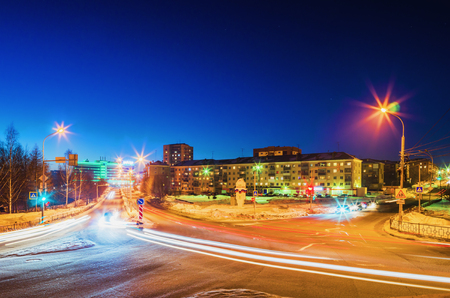NIZHNY TAGIL, RUSSIA - FEBRUARY 13, 2016: Light traces of passing cars at the intersection of roads in the city in the winter night