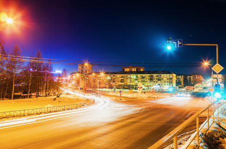 NIZHNY TAGIL, RUSSIA - FEBRUARY 13, 2016: The green light is lit on the traffic light at the intersection of roads in the winter in the dark Stock Photo
