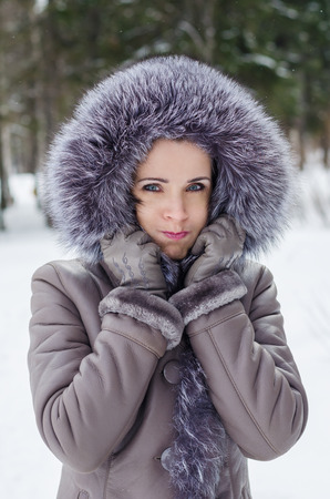 Beautiful woman in winter jacket with fur hood having fun, making a funny face c puffed-out cheeks Stock Photo