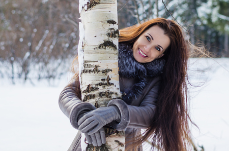 Beautiful joyful woman with her long hair peeking from behind the birch trees in winter forest photo