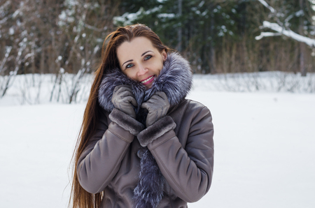 Beautiful woman with long hair in warm winter jacket standing on snowy forest glade. She looks into the camera lens and smiles photo