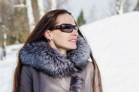 Beautiful woman in sunglasses standing in a Sunny wood glade in winter photo