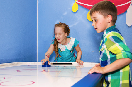children at play: Children intently and enthusiastically play table hockey.
