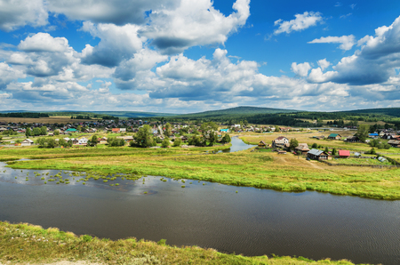 ural: Beautiful landscape with a village located on the banks of the river, on a summer day. Russia. Ural. The Village Of Staroutkinsk