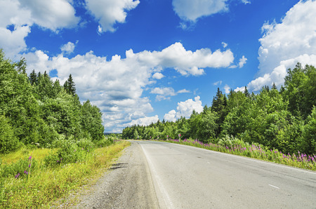 urals: Beautiful summer landscape with the road going for the turn and the white clouds in the blue sky.