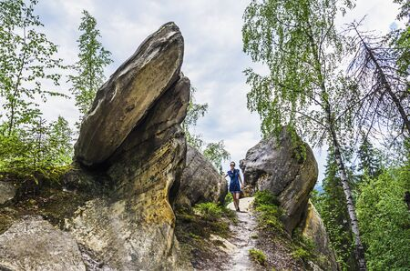 tourist stands at the top of the mountain among the rocks photo