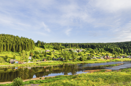 Rural landscape with village on a river on a summer evening. Russia. Perm Krai