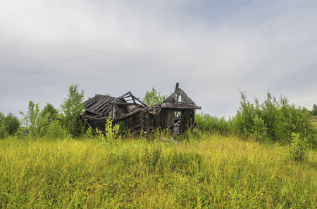 The ruins of the old wooden houses in a clearing in a summer cloudy day Stock Photo