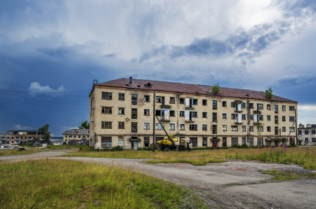 An abandoned house in a dying town  of Yubileyny on the background of dark cloudy sky. Russia, Perm Krai