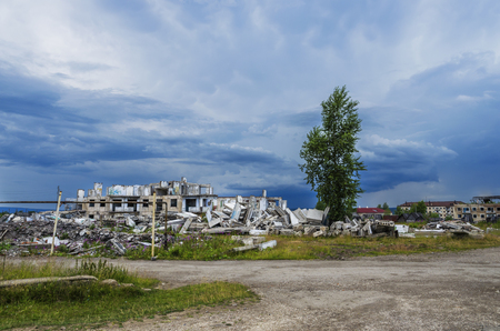 The ruins of a multistory building in the abandoned town of Yubileyny on the background of dark cloudy sky. Russia, Perm Krai