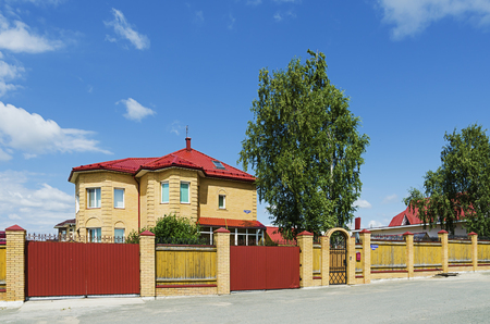 ural: SOLIKAMSK,  PERM KRAI, RUSSIA - JULY 14, 2016: Beautiful two-story cottage behind the fence in summer Sunny day