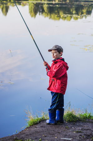 A boy stands on the shore of the pond early on a summer morning with a fishing rod