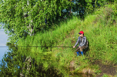 The woman-a fisherman standing with a fishing rod on the Bank of the pond on a summer morning photo